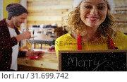 Купить «Video composition with falling snow over happy girl in cafe with greetings on board», видеоролик № 31699742, снято 2 ноября 2018 г. (c) Wavebreak Media / Фотобанк Лори
