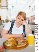 Купить «Fatty woman eating pizza in fastfood restaurant», фото № 31699954, снято 24 мая 2019 г. (c) Tryapitsyn Sergiy / Фотобанк Лори