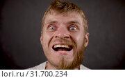 Handsome bearded hipster male smiles like crazy a in the black studio. Стоковое видео, видеограф Dzmitry Astapkovich / Фотобанк Лори