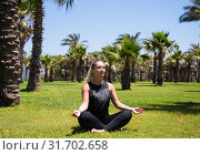 Купить «Girl doing yoga on the grass among palm trees», фото № 31702658, снято 17 февраля 2020 г. (c) Светлана Кузнецова / Фотобанк Лори