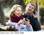 Купить «Mature couple with smartphones outdoors», фото № 31703166, снято 23 августа 2019 г. (c) Яков Филимонов / Фотобанк Лори