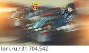 Купить «Man and women competing on racing cars», фото № 31704542, снято 18 марта 2019 г. (c) Яков Филимонов / Фотобанк Лори