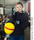 Купить «Female racer holding helmet on kart track», фото № 31704550, снято 18 марта 2019 г. (c) Яков Филимонов / Фотобанк Лори