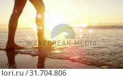 Woman walking barefoot in ocean on the sand against sunshine on ocean. Стоковое видео, агентство Wavebreak Media / Фотобанк Лори