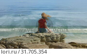 Купить «Red haired woman sitting by the beach», видеоролик № 31705354, снято 5 апреля 2019 г. (c) Wavebreak Media / Фотобанк Лори