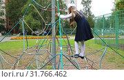 Купить «The school-girl in the uniform is climbing on the rope slide», видеоролик № 31766462, снято 12 марта 2019 г. (c) Aleksandr Sulimov / Фотобанк Лори