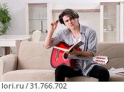 Купить «Young man with guitar at home», фото № 31766702, снято 17 января 2019 г. (c) Elnur / Фотобанк Лори