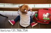 Купить «Girl sits at the wooden balcony and looks at children scampering about», видеоролик № 31766754, снято 1 сентября 2018 г. (c) Aleksandr Sulimov / Фотобанк Лори