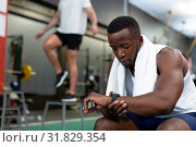 Купить «Male athletic checking time on watch in fitness center», фото № 31829354, снято 24 марта 2019 г. (c) Wavebreak Media / Фотобанк Лори