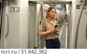 Купить «Young woman with a smartphone and headphones enters a subway car», видеоролик № 31842382, снято 25 апреля 2019 г. (c) Яков Филимонов / Фотобанк Лори
