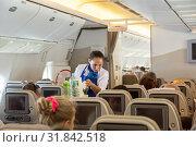 Стюардесса авиакомпании ИрАэро обслуживает пассажиров на борту самолета (2019 год). Редакционное фото, фотограф Юлия Бабкина / Фотобанк Лори