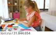 Купить «creative girl making greeting card at home», видеоролик № 31844654, снято 21 июля 2019 г. (c) Syda Productions / Фотобанк Лори