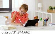Купить «girl with tablet pc writing to notebook at home», видеоролик № 31844662, снято 21 июля 2019 г. (c) Syda Productions / Фотобанк Лори