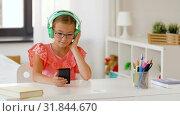 Купить «girl in headphones listening to music on cellphone», видеоролик № 31844670, снято 21 июля 2019 г. (c) Syda Productions / Фотобанк Лори