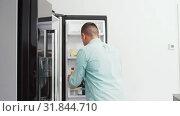 Купить «man taking juice from fridge at home kitchen», видеоролик № 31844710, снято 21 июля 2019 г. (c) Syda Productions / Фотобанк Лори