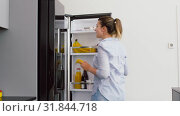 Купить «woman taking banana from fridge at home kitchen», видеоролик № 31844718, снято 21 июля 2019 г. (c) Syda Productions / Фотобанк Лори