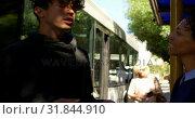 Купить «Couple interacting with each other at bus stop 4k», видеоролик № 31844910, снято 10 июня 2018 г. (c) Wavebreak Media / Фотобанк Лори