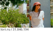 Beautiful woman leaning on pillar in the city 4k. Стоковое видео, агентство Wavebreak Media / Фотобанк Лори