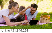 Купить «family with tablet pc on picnic in summer park», видеоролик № 31846254, снято 21 июля 2019 г. (c) Syda Productions / Фотобанк Лори