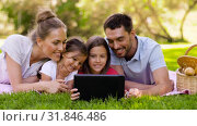 Купить «family with tablet pc on picnic in summer park», видеоролик № 31846486, снято 24 июля 2019 г. (c) Syda Productions / Фотобанк Лори