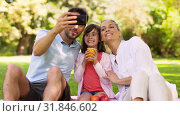 Купить «family having picnic and taking selfie at park», видеоролик № 31846602, снято 21 июля 2019 г. (c) Syda Productions / Фотобанк Лори