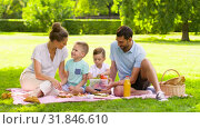 Купить «happy family eating fruits on picnic at park», видеоролик № 31846610, снято 21 июля 2019 г. (c) Syda Productions / Фотобанк Лори