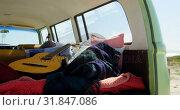 Купить «Guitar, cloths and blanket in van 4k», видеоролик № 31847086, снято 20 сентября 2018 г. (c) Wavebreak Media / Фотобанк Лори
