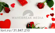 Купить «Red roses, gift boxes and heart shape of confetti on white surface in circle formation 4k», видеоролик № 31847210, снято 11 октября 2018 г. (c) Wavebreak Media / Фотобанк Лори