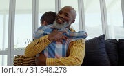 Front view of mature black father embracing his son in living room of comfortable home 4k. Стоковое видео, агентство Wavebreak Media / Фотобанк Лори