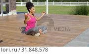 Side view of young mixed-race woman doing yoga in backyard of home 4k. Стоковое видео, агентство Wavebreak Media / Фотобанк Лори