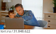 Купить «Front view of young Caucasian father helping son with homework at table in a comfortable home 4k», видеоролик № 31848622, снято 6 ноября 2018 г. (c) Wavebreak Media / Фотобанк Лори