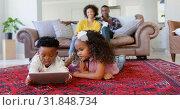 Купить «Front view of cute black kids using digital tablet in living room at  comfortable home 4k», видеоролик № 31848734, снято 7 ноября 2018 г. (c) Wavebreak Media / Фотобанк Лори