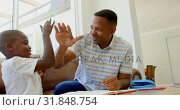 Купить «Front view of young black father helping his son with homework in a comfortable home 4k», видеоролик № 31848754, снято 7 ноября 2018 г. (c) Wavebreak Media / Фотобанк Лори