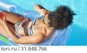 Купить «High angle view of young mixed-race woman wearing sunglasses while relaxing on floating pool lounger», видеоролик № 31848766, снято 7 ноября 2018 г. (c) Wavebreak Media / Фотобанк Лори