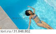 Купить «High angle view of young mixed-race woman floating in swimming pool on a sunny day 4k», видеоролик № 31848802, снято 7 ноября 2018 г. (c) Wavebreak Media / Фотобанк Лори