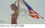 Купить «Side view of young Caucasian woman holding a American flag on the beach 4k», видеоролик № 31857858, снято 6 ноября 2018 г. (c) Wavebreak Media / Фотобанк Лори