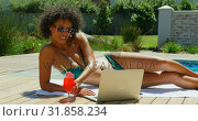 Купить «Side view of young black woman using laptop near swimming pool 4k», видеоролик № 31858234, снято 7 ноября 2018 г. (c) Wavebreak Media / Фотобанк Лори