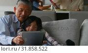 Купить «Front view of cute asian granddaughter and old senior grandfather using digital tablet at home 4k», видеоролик № 31858522, снято 18 октября 2018 г. (c) Wavebreak Media / Фотобанк Лори