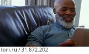 Купить «Front view of mature black man using digital tablet in a comfortable home 4k», видеоролик № 31872202, снято 7 ноября 2018 г. (c) Wavebreak Media / Фотобанк Лори