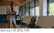 Купить «Front view of young black businessman writing on document in office 4k», видеоролик № 31872770, снято 1 октября 2018 г. (c) Wavebreak Media / Фотобанк Лори