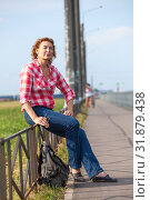 Купить «Mature woman hitchhiker sitting near road and waiting the car for ride», фото № 31879438, снято 21 июня 2019 г. (c) Кекяляйнен Андрей / Фотобанк Лори