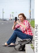 Купить «Женщина средних лет, сидящая на обочине городской дороги, фотографирует на смартфон», фото № 31879442, снято 21 июня 2019 г. (c) Кекяляйнен Андрей / Фотобанк Лори