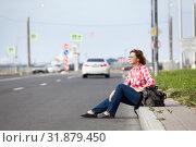 Купить «Hitchhiking, passenger car driving along, woman sitting roadside with backpack», фото № 31879450, снято 21 июня 2019 г. (c) Кекяляйнен Андрей / Фотобанк Лори