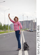 Middle age woman hail a taxi on road, stands on lane with backpack on asphalt. Стоковое фото, фотограф Кекяляйнен Андрей / Фотобанк Лори