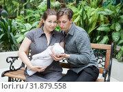 Купить «Portrait of happy parents with newborn baby in hands, sitting on bench in plants», фото № 31879558, снято 15 июня 2019 г. (c) Кекяляйнен Андрей / Фотобанк Лори