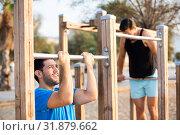 Купить «Two friends 30 years old are doing pull-ups for strength», фото № 31879662, снято 6 сентября 2017 г. (c) Яков Филимонов / Фотобанк Лори