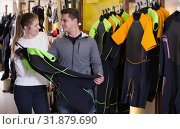 Купить «Woman assistant is helping man choose new costume for diving», фото № 31879690, снято 25 января 2018 г. (c) Яков Филимонов / Фотобанк Лори