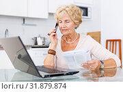 Купить «Woman talking on phone, using laptop», фото № 31879874, снято 11 июля 2018 г. (c) Яков Филимонов / Фотобанк Лори