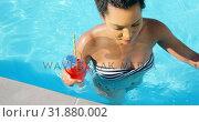 Купить «High angle view of young mixed-race woman walking with cocktail glass in swimming pool 4k», видеоролик № 31880002, снято 7 ноября 2018 г. (c) Wavebreak Media / Фотобанк Лори