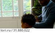 Купить «Side view of cute little black son waking from fathers lap while sitting on the couch in a comfortab», видеоролик № 31880022, снято 19 октября 2018 г. (c) Wavebreak Media / Фотобанк Лори